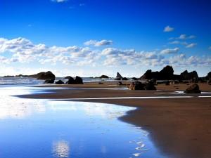 Postal: Rocas en una extensa playa