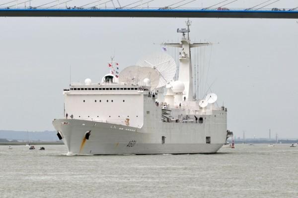 Impresionante embarcación militar navegando bajo un puente