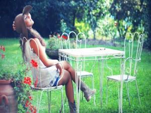Chica sentada en una silla del jardín