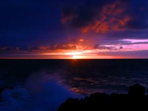 Postal: El sol del amanecer iluminando poco a poco el mar