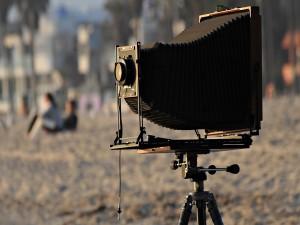 Postal: Antigua cámara de fotos en una playa