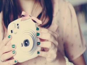 Chica sosteniendo una cámara de fotos Fujifilm