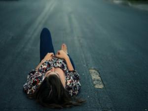 Mujer tendida sobre una carretera