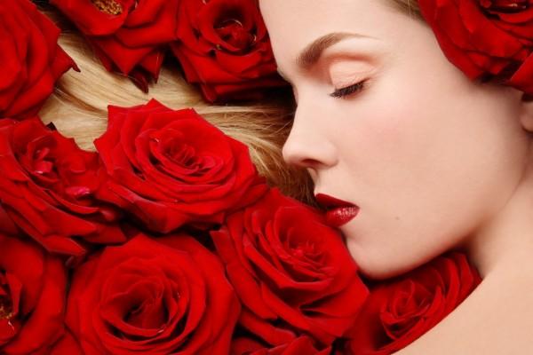 Bella mujer dormida entre rosas rojas