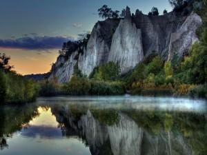 Rocas y árboles reflejados en el agua