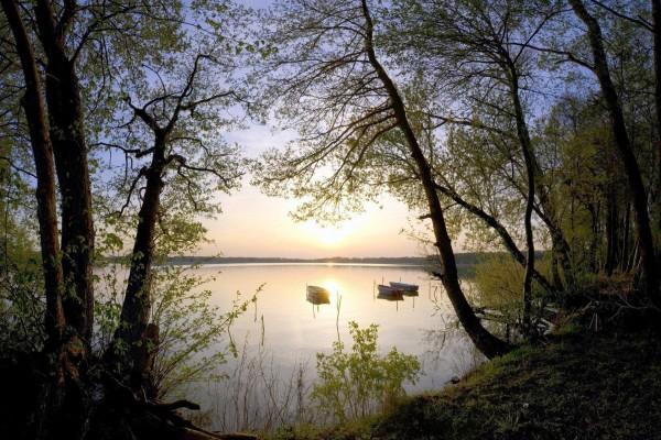 Sol brillando junto a unas barcas ancladas en el lago
