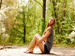 Postal: Chica descansando en un bosque