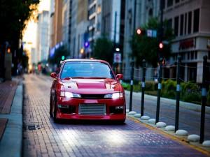 Postal: Un coche rojo con las luces encendidas