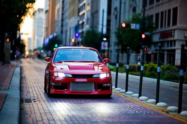 Un coche rojo con las luces encendidas