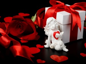 Postal: Cupido junto a un regalo para el Día de San Valentín