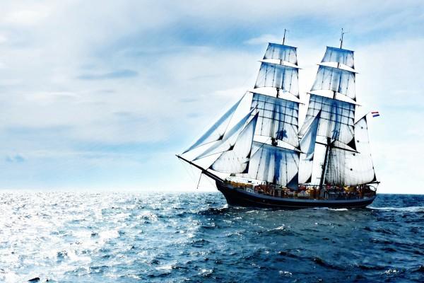 Barco con grandes velas navegando en el mar
