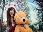 Chica feliz con su gran oso de peluche