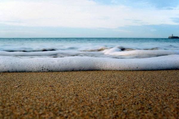 Espuma de mar sobre la arena de una playa