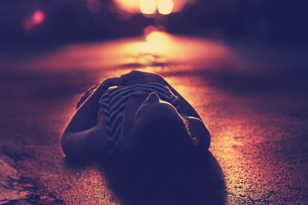 Mujer tumbada en el asfalto