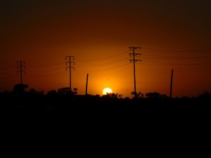 Postal: El sol del atardecer tras un tendido eléctrico