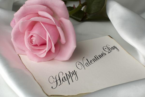 Rosa sobre una nota de ¡Feliz Día de San Valentín!