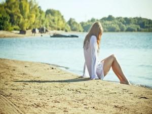 Mujer sentada junto al agua
