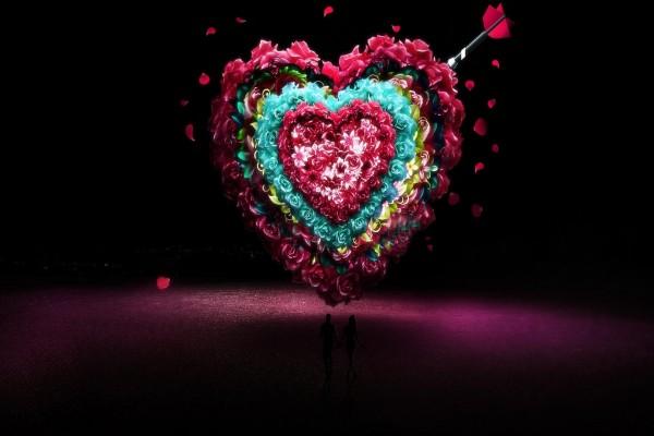 Un gran corazón de flores sobre una pareja de enamorados