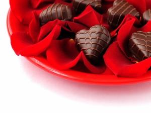 Postal: Bombones de chocolate sobre pétalos de rosas