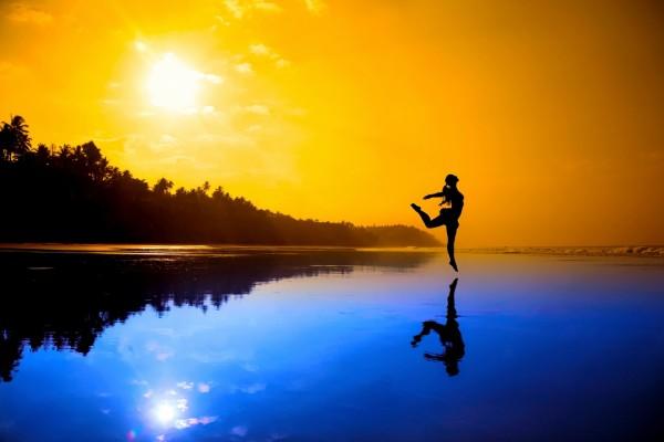 Silueta de una mujer danzando en una playa al atardecer