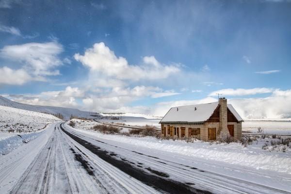 Casa junto a una carretera cubierta de nieve
