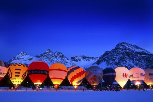 Globos aeroestáticos iluminados sobre la nieve