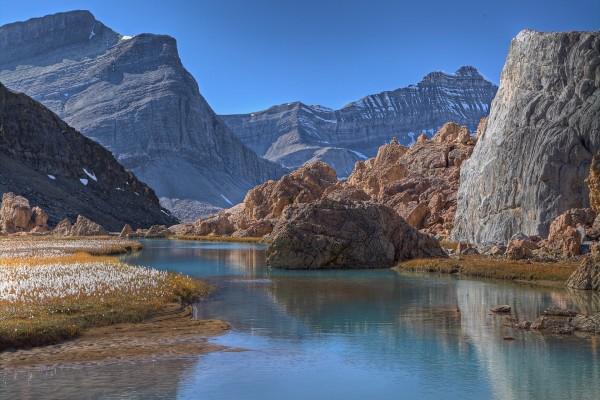 Agua cristalina corre entre rocas y montañas