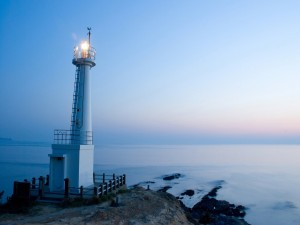 Postal: Faro iluminado al amanecer