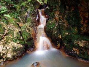 Estrecha cascada entre rocas con musgo