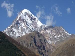 Nubes sobre el pico de una montaña cubierto de nieve