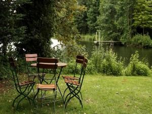 Mesa y sillas en el jardín junto a un bello y tranquilo lago