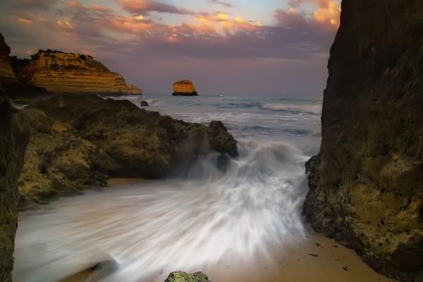 Agua entrando a la playa entre las rocas
