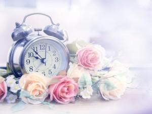 Postal: Rosas junto a un reloj marcando las horas mágicas