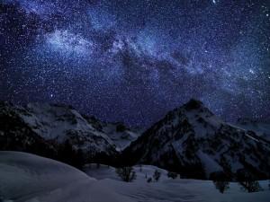 Cielo estrellado sobre las montañas nevadas