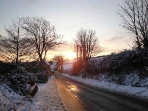 Sol iluminando una carretera en invierno
