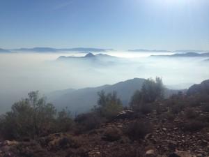 Postal: El sol brillando sobre las nubes que cubren las montañas