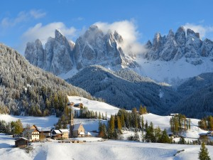 Pueblo cubierto de nieve junto a las montañas