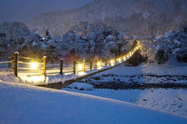 Puente iluminado en una noche de nieve