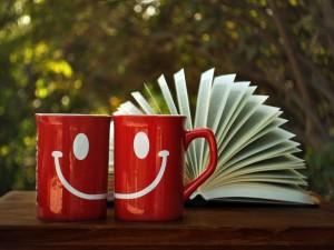 Postal: Dos tazas sonrientes junto a un libro