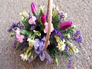 Tulipanes, claveles y narcisos en una canasta