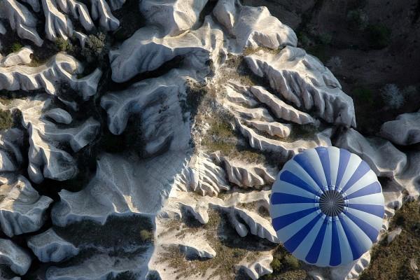 Globo aeroestático volando sobre una zona rocosa