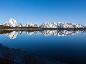 Postal: Montañas reflejadas en un lago en calma