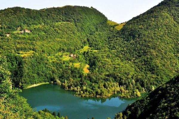Lago rodeado por montañas y árboles verdes