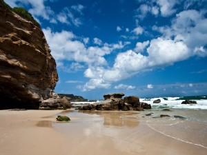 Postal: Nubes blancas sobre una playa rocosa