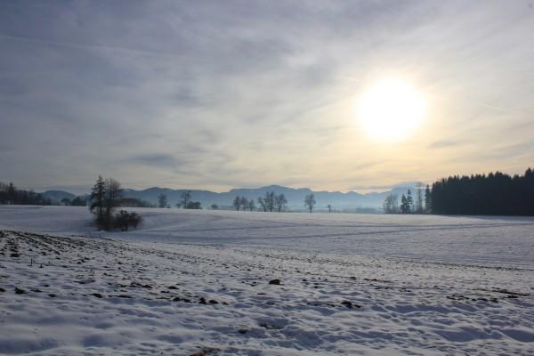 El sol entre las nubes sobre un paisaje cubierto de nieve