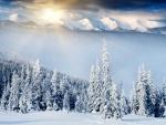 El sol tras las montañas iluminando el paisaje nevado