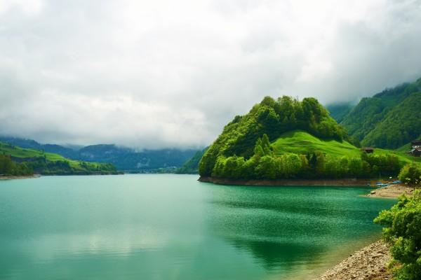 Nubes bajas sobre un lago verde