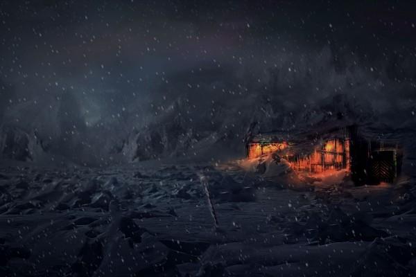 Cabaña iluminada bajo la nieve