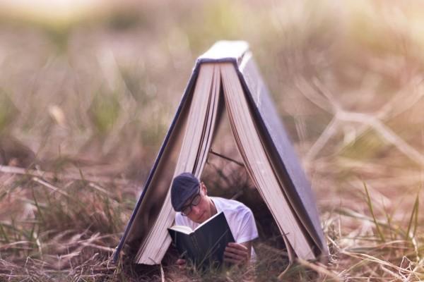 Chico leyendo bajo un gran libro