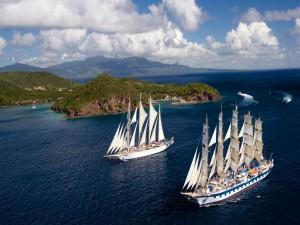 Postal: Dos barcos con grandes velas navegando en un bello mar azul